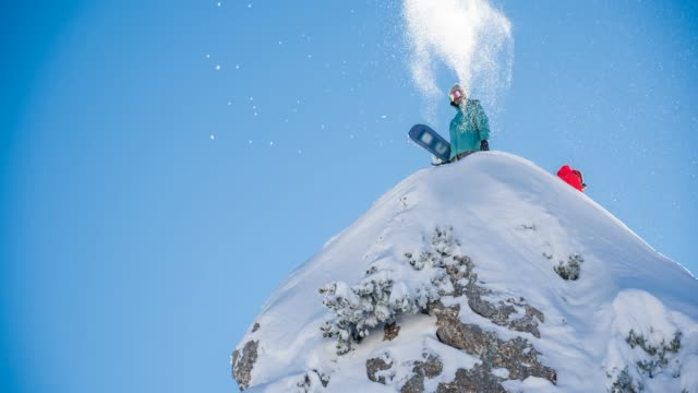 snowboarder standing on top of snowcapped mountain, throwing snow in the air - snowboard stock videos and b-roll footage