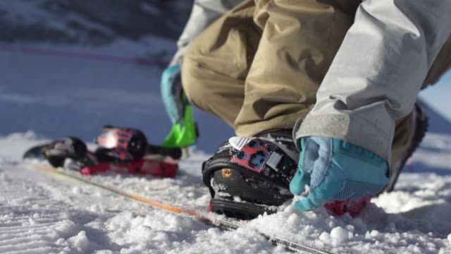 snowboarder strapping in - snowboarding stock videos & royalty-free footage