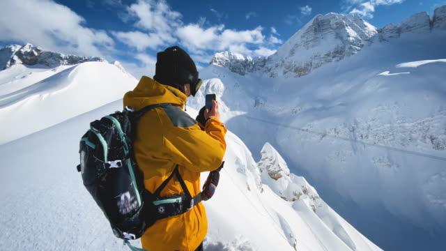 山の尾根の上にスマートフォンで写真を撮るスノーボーダー - 冠雪点の映像素材/bロール