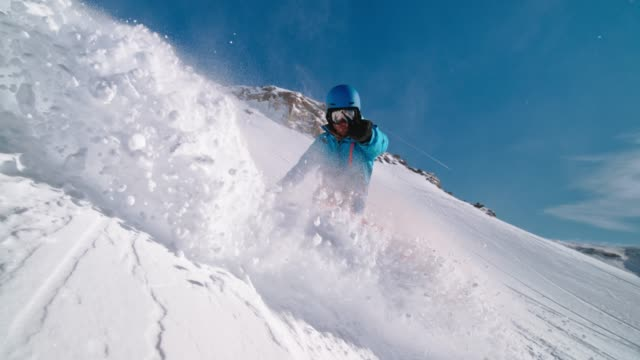 slo mo snowboarder turning on the slope and causing a powder splash - powder snow stock videos and b-roll footage