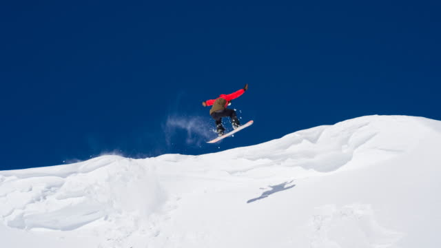 snowboarder unsuccessfully performing a stunt, falling - snowboard video stock e b–roll