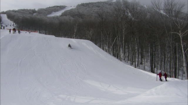 snowboarders and skiers enjoy snowy slopes in vermont. - winter sport stock videos & royalty-free footage