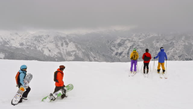 vídeos de stock e filmes b-roll de aerial snowboarders and skiers on the snowy mountain top - roupa de esqui