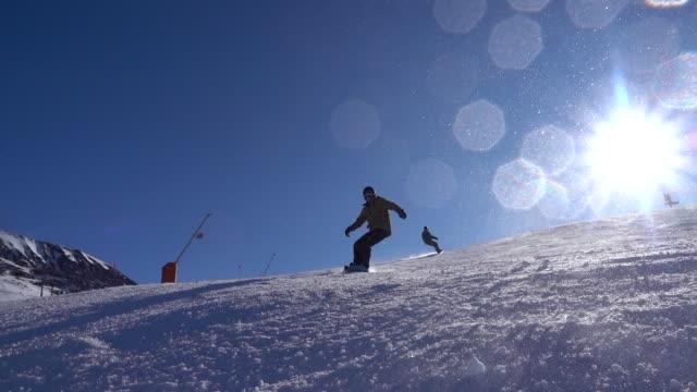 snowboarders crank turns on ski slope, create snow spray - powder snow stock videos & royalty-free footage
