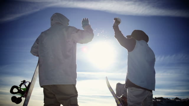 snowboarders high fiving on top of a mountain - snowboarding stock videos & royalty-free footage