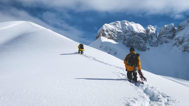 スノーボーダーが上り坂の雪山をハイキング - 冠雪点の映像素材/bロール