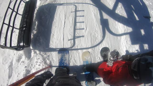 POV of snowboarders on a ski lift at a ski resort. - Slow Motion