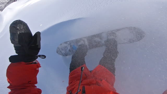 Snowboarders point of view, spraying snow into camera