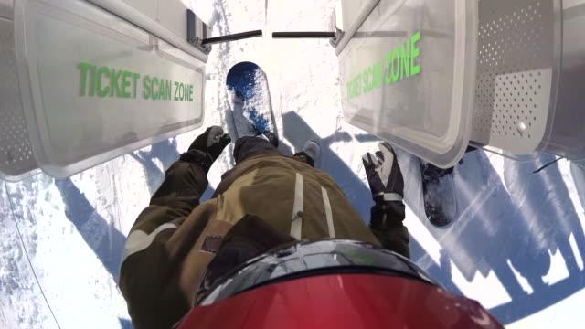 pov of snowboarders riding on a lift at a ski resort. - wintermantel stock-videos und b-roll-filmmaterial