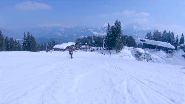 snowboarding at a ski resort man riding snow covered mountain. - slow motion - ski resort stock videos & royalty-free footage