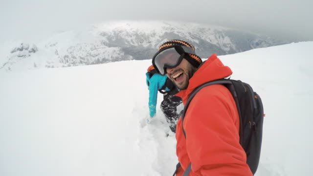 POV Snowboarding couple making a video in powder snow