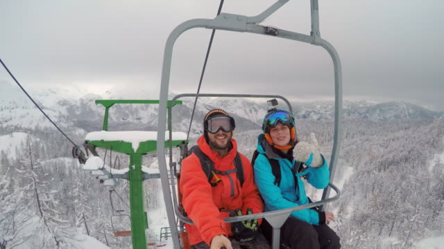 vídeos de stock e filmes b-roll de pov snowboarding couple riding a chairlift and making a video - casaco de esqui