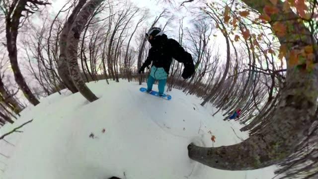 snowboarding friends enjoying a ride through a snowy forest - ski holiday stock videos & royalty-free footage