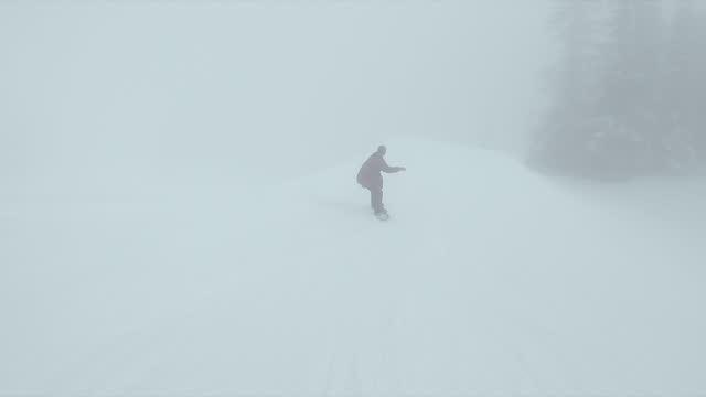 snowboarding in fog at a ski resort man riding snow covered mountain. - freizeitaktivität stock-videos und b-roll-filmmaterial