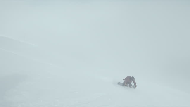 snowboarding in fog at a ski resort man riding snow covered mountain. - slow motion - ski resort stock videos & royalty-free footage