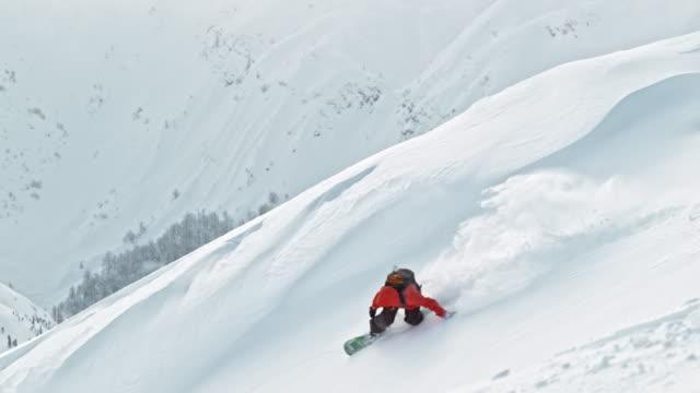 SLO MO Snowboarding in powder snow on mountain top