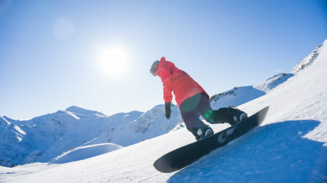snowboarding on a snowcapped mountain on a beautiful sunny day - snowboard video stock e b–roll