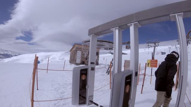 snowboarding ski lift at a ski resort man riding snow covered mountain. - slow motion - ski resort stock videos & royalty-free footage