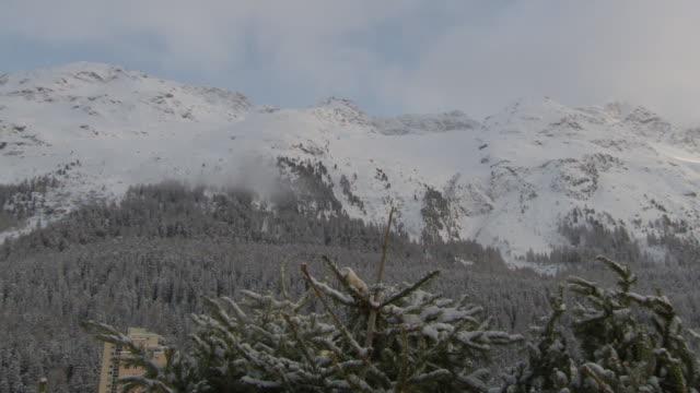 snowcapped alps mountain range evergreen trees fg blue sky w/ white gray clouds bg winter alpine - sockel stock-videos und b-roll-filmmaterial