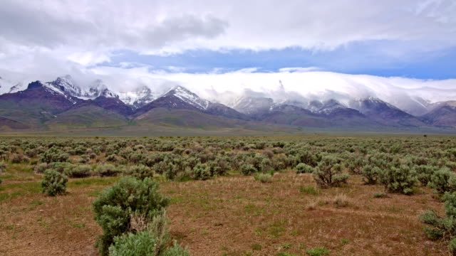 Snowcapped desert mountains and clouds spring Steens Mountain from Alvord Desert and sagebrush