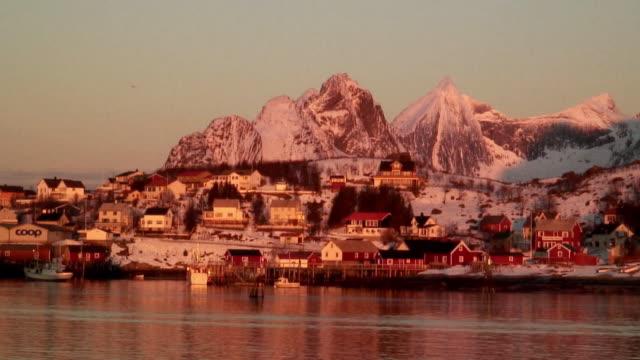 ws snowcapped mountain peak rising above seaside village at sunrise / reine, lofoten, norway - unknown gender stock videos & royalty-free footage