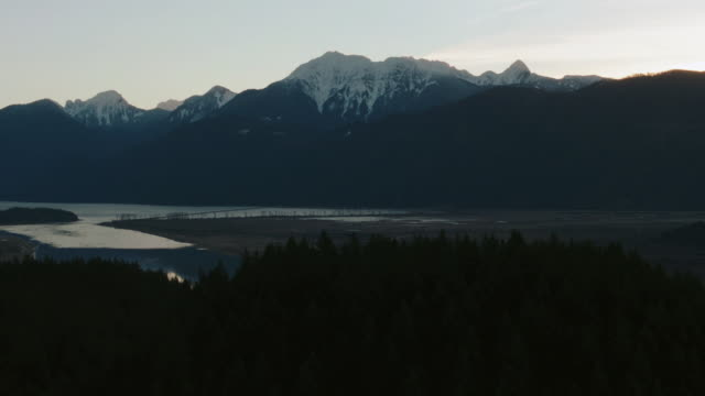 stockvideo's en b-roll-footage met aerial snow-capped mountain peaks reflecting in the still waters below / united states - letterbox format
