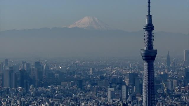 aerial, snowcapped mt fuji beyond tokyo skyline, japan - tokyo japan stock videos & royalty-free footage