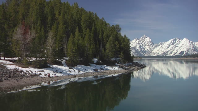 WS Snowcapped Teton mountain range from Yellowstone National Park, mountains reflecting in lake / Jackson, Wyoming, USA