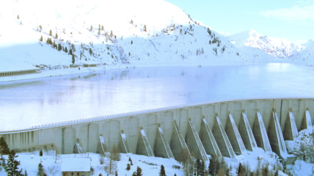 snow-covered alps surround a reservoir on lake fedaia. - dam stock videos & royalty-free footage