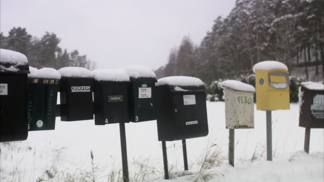 snow-covered mailboxes in a row, sweden. - mailbox stock videos and b-roll footage