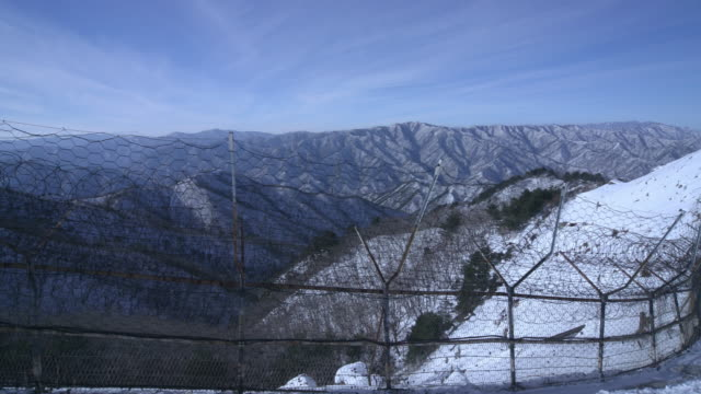 snow-covered mountain next to the military demarcation line in winter/ dmz (demilitarized zone between south and north korea), goseong-gun - chainlink fence stock videos and b-roll footage