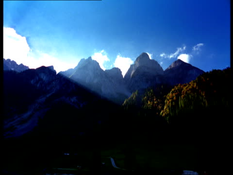 snow-covered mountain peaks rise behind wooded hills in autumn colors. - 水の形態点の映像素材/bロール