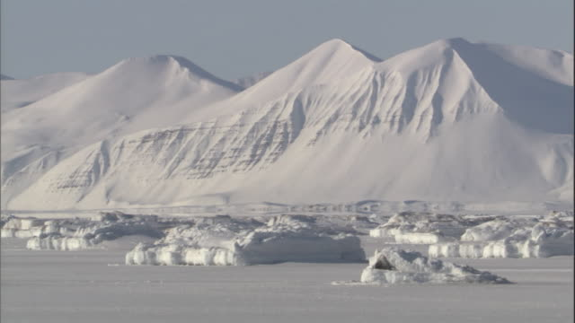 a snow-covered mountain range stands out against a flat blue sky. - svalbard and jan mayen stock videos & royalty-free footage