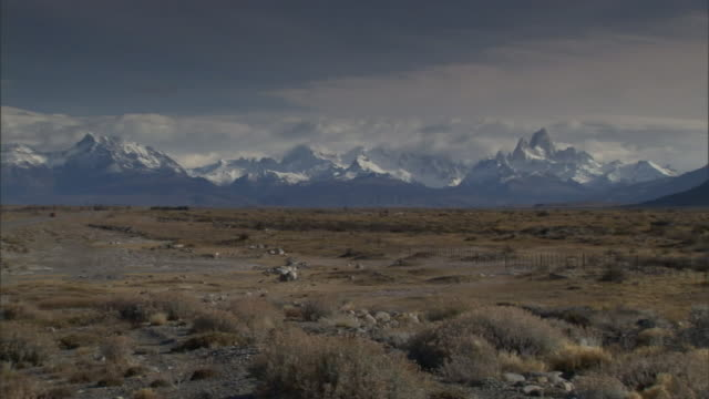 snow-covered mountains border a scrub desert. - shrubland stock videos & royalty-free footage