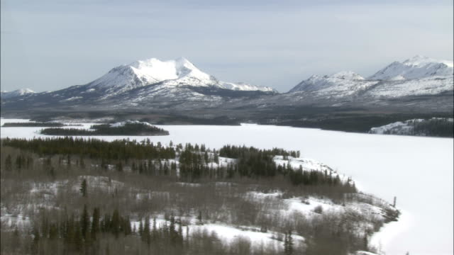 snow-covered mountains surround a frozen tagish lake. - whitehorse stock videos and b-roll footage