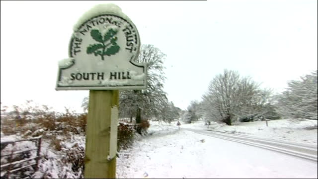 snow-covered national trust sign 'south hill' long shot of abandoned vehicles in snowy landscape - national trust video stock e b–roll