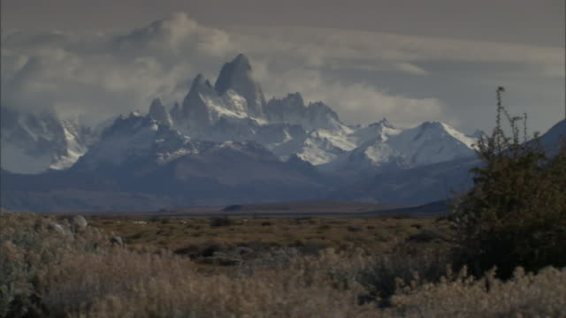 snow-covered peaks loom beyond a scrub desert. - shrubland stock videos & royalty-free footage