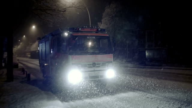snowfall at night with fire truck slow motion - feuerwache stock-videos und b-roll-filmmaterial