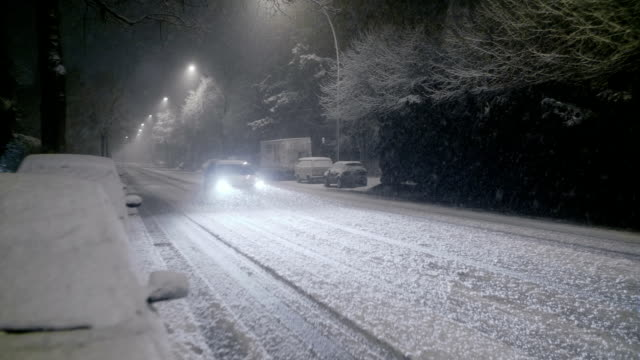 snowfall at night with traffic slow motion - taxi stock-videos und b-roll-filmmaterial