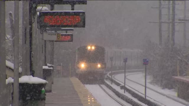 snowfall in long island a train approaches a snowy station platform on december 10 2013 in hempstead new york - long island railroad stock videos and b-roll footage