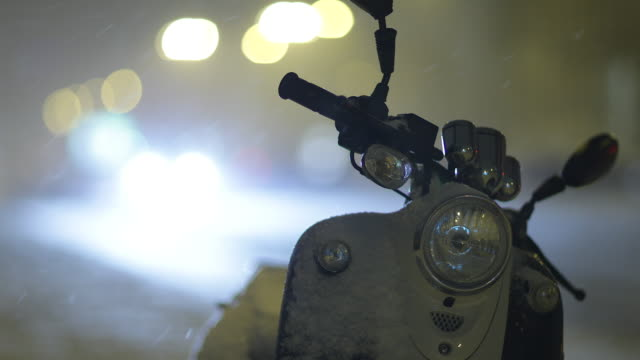 Snowfall with a Motorcycle with Bokeh Lights and Traffic