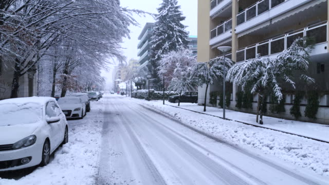 snowing on a city street with cars and building - urban road stock videos & royalty-free footage