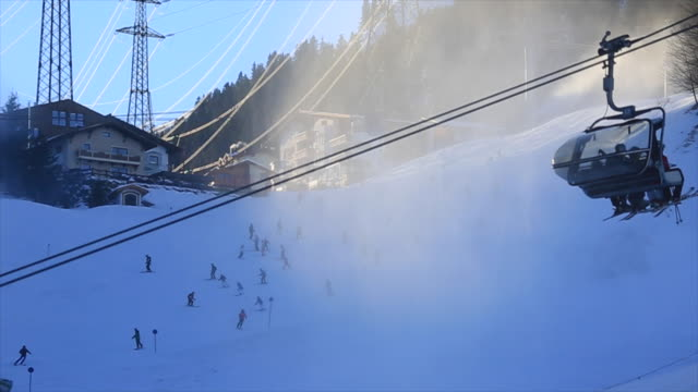 snow-making machines a snow covered mountain resort. - seggiovia video stock e b–roll