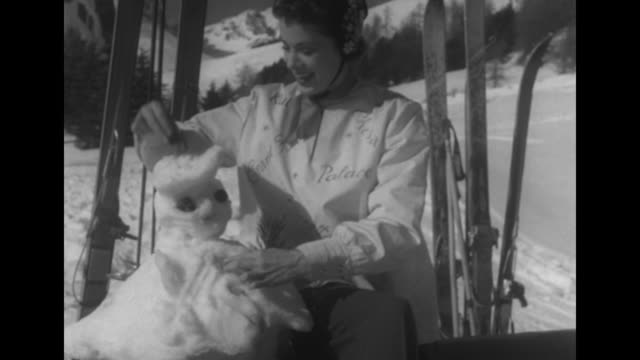vídeos de stock, filmes e b-roll de snowman on an outdoor table surrounded by skis / models decorate snowman put cigarette in its mouth model pam smiles she wears a geny spielmann ski... - 1950