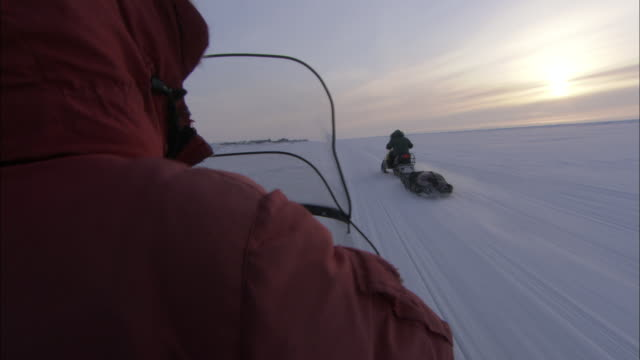 a snowmobile driver follows another snowmobile that pulls a sled. - winter sport stock videos & royalty-free footage