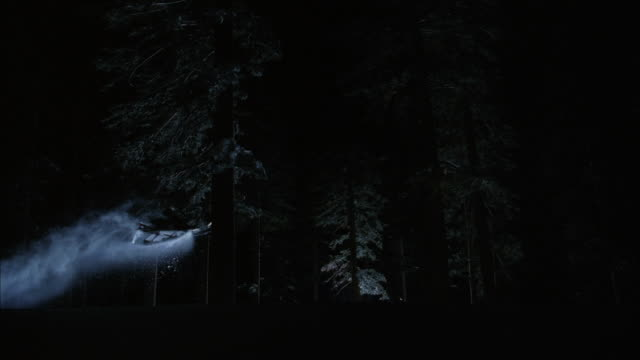 ws slo mo snowmobile jumping in snow covered forest / mammoth lakes, california, usa - mammoth lakes video stock e b–roll
