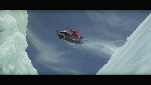 ws la pan snowmobile jumping over crevasse - letterbox format stock videos & royalty-free footage