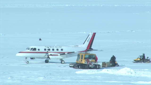 snowmobiles haul equipment near a parked snow cat and plane the arctic september 21 2008 – from the historic 17month expedition involving 250... - 商業車点の映像素材/bロール