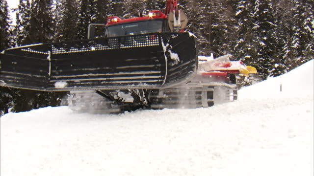 A snowplow travels past the camera.