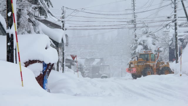snowplow works to clear streets of deep snow during blizzard in japan - buried stock videos & royalty-free footage